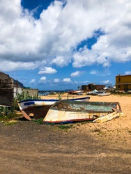 Wrecks of two small old wooden fishing boats on the golden sandy beach of the capital of Tenerife, above the blue clouds. Beautiful Las Teresitas Beach in San Andrés, Santa Cruz de Tenerife. Spain