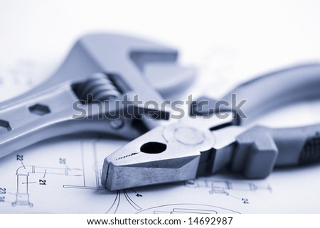 wrench and pliers over technical drawing toned blue