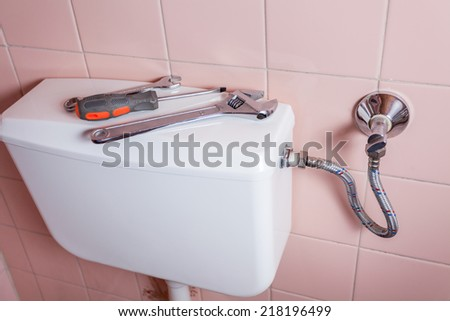 Wrench spanner and screwdiver lying on a toilet