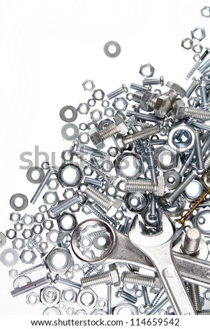 Wrenches, nuts and bolts on plain background
