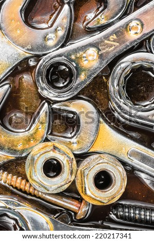 Wrenches, nuts, bolts and screws stained with motor oil