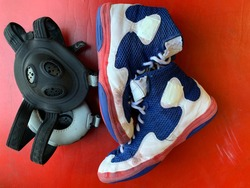 Wrestling shoes and headgear on a wrestling mat.