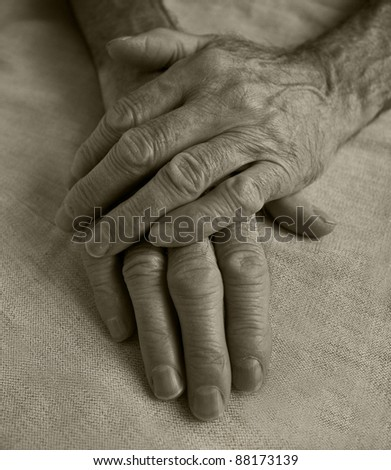 wrinckled hands of old man on light fabric