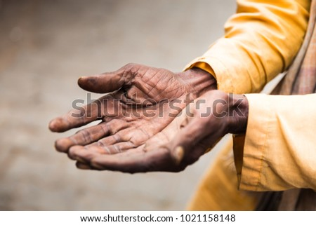 Wrinkled old hands of an unknown, yellow dressed, indian brahman who is begging for money. CloseUp of hands with softfocus background. Human emotions with body language and reaction. Charity and help.