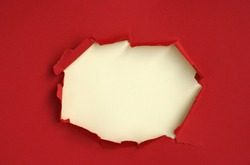 Wrinkled ripped torn red paper with hole in center background texture poster backdrop empty space