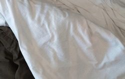 Wrinkled white cloth covers other cloth, messy pile of cloth.