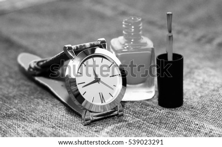 Wrist watch and nail Polish on jeans background