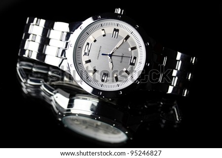 Wrist watch lying on dark background - stock photo
