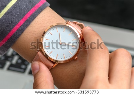 Wrist watch on girl's hand in front of a laptop computer