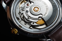 Wrist watch with metal gears and cogwheels. Clock mechanism macro shot.