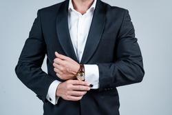 Wristlet watch worn on male arm wrist in formal fashion tuxedo grey background, timepiece.