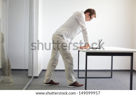 wrists exercise durring office work standing man reading at tablet in his office