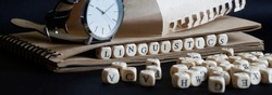 Wristwatch, eco-friendly notepad and the word linguistics made of wooden cubes on a dark. Concept for scientific research in linguistics and teaching at school or college. Web banner