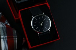 wristwatch in a red box on a dark background.Set of men's accessories,necktie, perfumes and watch on a black background