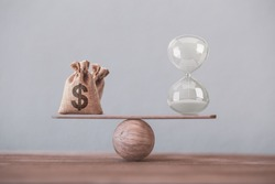Write sand clock or hourglass and dollar bagson a balance scale in equal position on wood table. Financial concept : Time value of money, asset growth over time, depicts investment in long-term equity