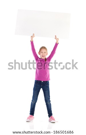 Write your message on white banner. Cute little girl holding blank banner over her head and shouting. Full length studio shot isolated on white.