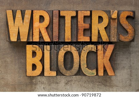 writer block - text in vintage wood letterpress printing blocks stained by color inks on a grunge metal tray
