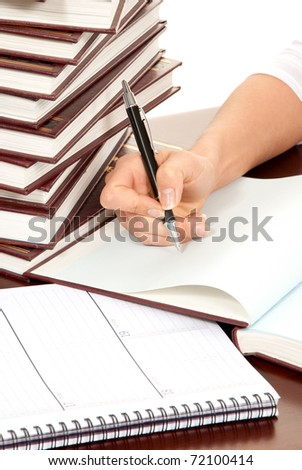 Writer business person hand with pen signing document. On the table stack of books organizer notebook on white background