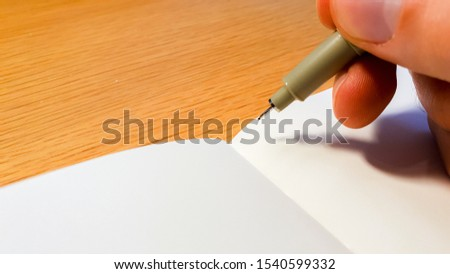 Writer getting over writers block and starting fresh on a blank page in a note book with an ink pen