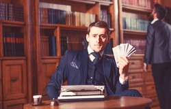 Writer got honorarium for new book. Writer or author with strict face with typewriter in library with books on background, defocused. Writing and fees concept. Man in oldfashioned suit holds money.