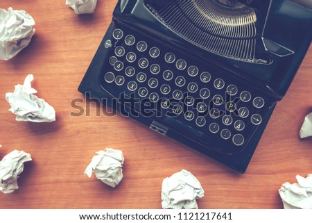 Writer's block concept with typewriter and crumpled paper on work desk