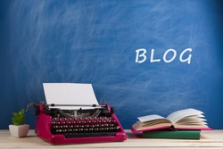 writer's workplace - crimson typewriter and books on blue blackboard background with text