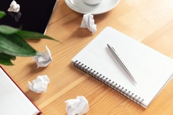 Writer workplace with notepad and pen. Crumpled papers, clear sheet in notebook on wooden table. Business planning and brainstorming. Creation process and authorship concept