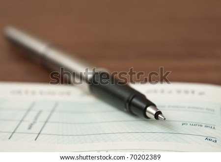 Writing a cheque- very shallow depth of field with focus of tip of pen