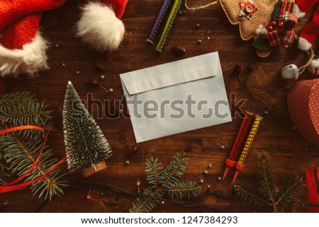Writing a letter to Santa Claus for Christmas, blank envelope on table among festive holiday decoration #1247384293