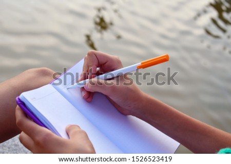 Writing a personal diary. The girl keeps a secret diary. Female hand writes a letter on the lake. Writing our thoughts in a notebook. Writing memoirs and poems