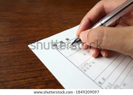 Photo of  Writing a resume. On the resume form, the items to be filled in each column such as name, date of birth, address, etc. are shown in Japanese.