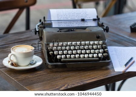 Writing and freelance concept. Retro typeweriter, paper with pencils and a cup of cappuccino on wooden table. #1046944450