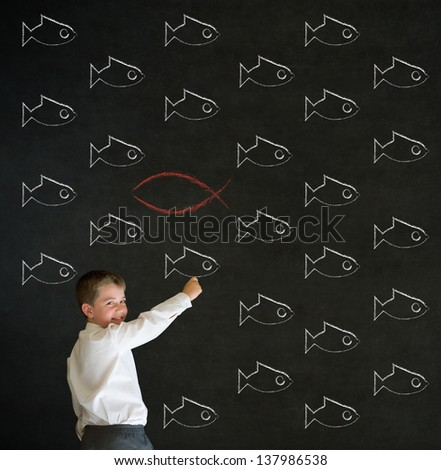 Writing boy dressed up as business man with independent thinking Jesus, God, Christianity fish on blackboard background