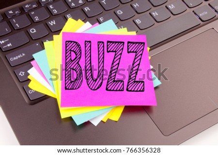 Writing Buzz text made in the office close-up on laptop computer keyboard. Business concept for Buzz Word Workshop on the black background with space
