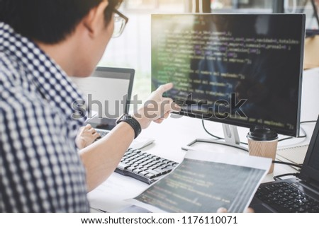 Writing codes and typing data code technology, Programmer cooperating working on web site project in a software developing on desktop computer at company. #1176110071