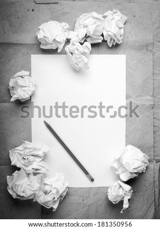 Writing concept - crumpled up paper wads with a sheet of white paper and pencil in black and white Zdjęcia stock ©