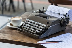 Writing concept. Gray retro typewriter on wooden tabletop, with a cup of cappuccino and paper with editing marks.