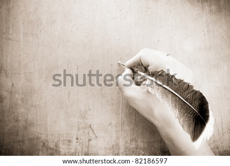writing hand and pen feather on wood background