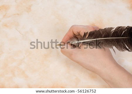 writing hand with feather at paper