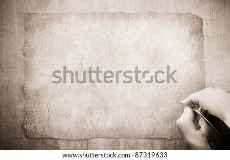 writing hand with feather on old paper parchment background