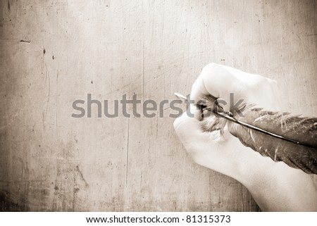 writing hand with pen feather on sepia