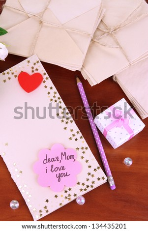 Writing letter of congratulations to mother's Day on wooden table close-up - stock photo