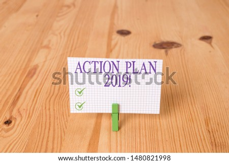 Writing note showing Action Plan 2019. Business photo showcasing proposed strategy or course of actions for current year Wooden floor background green clothespin groove slot office. #1480821998