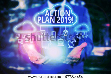 Writing note showing Action Plan 2019. Business photo showcasing proposed strategy or course of actions for current year Male wear formal work suit presenting presentation smart device. #1577234656