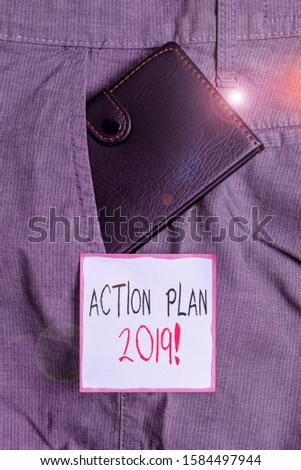 Writing note showing Action Plan 2019. Business photo showcasing proposed strategy or course of actions for current year Small wallet inside trouser front pocket near notation paper.