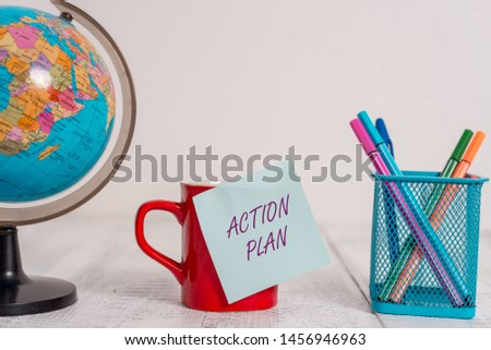 Writing note showing Action Plan. Business photo showcasing proposed strategy or course of actions for certain time Globe map world earth coffee cup sticky note pens holder wooden table. #1456946963