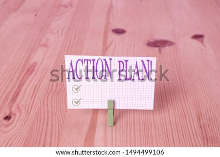 Writing note showing Action Plan. Business photo showcasing proposed strategy or course of actions for certain time Wooden floor background green clothespin groove slot office.