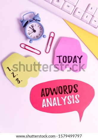 Writing note showing Adwords Analysis. Business photo showcasing monitor campaigns and ensuring investment returns in ads Flat lay with copy space on bubble paper clock and paper clips.