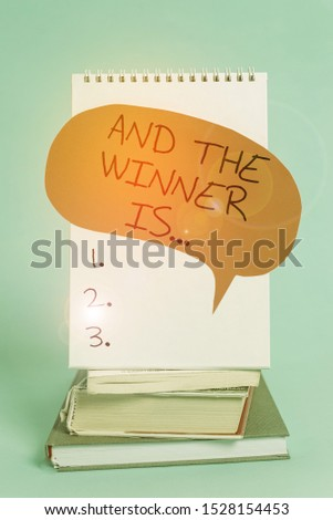 Writing note showing And The Winner Is. Business photo showcasing announcing a demonstrating or thing that wins something Spiral notebook speech bubble stacked old books cool pastel background.