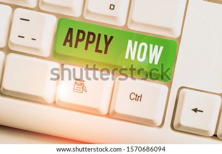 Writing note showing Apply Now. Business photo showcasing An act of a demonstrating to acquire the job related to the profession White pc keyboard with note paper above the white background.